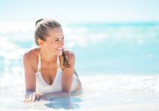 Lächelnde junge Frau, die an der Küste sitzt Lizenzfreie Stockbilder