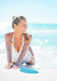 Lächelnde junge Frau, die an der Küste sitzt Lizenzfreies Stockbild