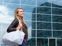 Lächelnde junge Frau, die in die Stadt mit Tasche geht Lizenzfreies Stockfoto