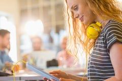 Lächelnde junge Frau, die digitale Tablette verwendet Stockfotos