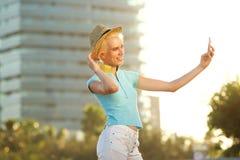 Lächelnde junge Frau, die draußen selfie Porträt nimmt Stockbild