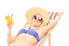 Lächelnde junge Frau, die ein Cocktail ein Sonnenbad nimmt und hält Stockfotografie
