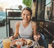 Lächelnde junge Frau, die ein englisches Frühstück isst stockfotografie