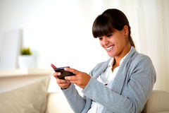 Lächelnde junge Frau, die eine Meldung durch Mobiltelefon sendet stockfotos