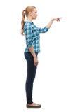 Lächelnde junge Frau, die etwas in der Luft wählt Lizenzfreies Stockbild