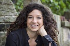 Lächelnde junge Frau, die gegen Steinwand stillsteht Stockbilder