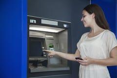 Lächelnde junge Frau, die Geld vom ATM zurücknimmt lizenzfreie stockfotografie