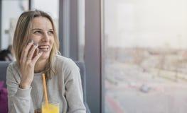 Lächelnde junge Frau, die am Handy Innen, schauend auf s spricht lizenzfreies stockfoto