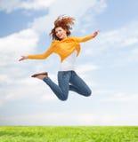 Lächelnde junge Frau, die hoch in einer Luft springt Stockfotos