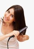 Lächelnde junge Frau, die ihr Haar geraderichtet Stockbild