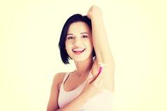 Lächelnde junge Frau, die ihre Achselhöhle rasiert Lizenzfreie Stockfotografie