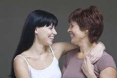 Lächelnde junge Frau, die ihre Mutter umfasst Stockfotografie