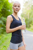 Lächelnde junge Frau, die ihren Bruch nachdem dem Laufen hat Lizenzfreies Stockbild