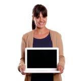 Lächelnde junge Frau, die ihren Laptop anhält und zeigt stockfoto