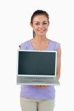 Lächelnde junge Frau, die ihren Laptop zeigt lizenzfreies stockbild