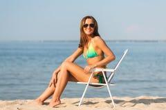 Lächelnde junge Frau, die im Aufenthaltsraum auf Strand ein Sonnenbad nimmt lizenzfreies stockfoto