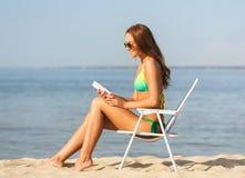 Lächelnde junge Frau, die im Aufenthaltsraum auf Strand ein Sonnenbad nimmt stockbild