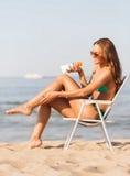 Lächelnde junge Frau, die im Aufenthaltsraum auf Strand ein Sonnenbad nimmt lizenzfreies stockbild