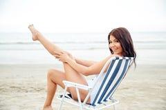 Lächelnde junge Frau, die im Aufenthaltsraum auf Strand ein Sonnenbad nimmt lizenzfreie stockfotos