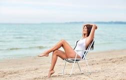 Lächelnde junge Frau, die im Aufenthaltsraum auf Strand ein Sonnenbad nimmt stockbilder