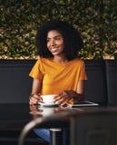 Lächelnde junge Frau, die im Café sitzt stockfotos