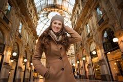 Lächelnde junge Frau, die im Galleria Vittorio Emanuele II steht Stockfotografie