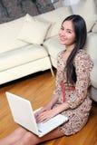Lächelnde junge Frau, die im Wohnzimmeresprit sitzt Lizenzfreie Stockbilder