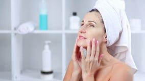 Lächelnde junge Frau, die kosmetische Maske und das Massieren des Gesichtes entfernt stock video
