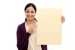 Lächelnde junge Frau, die leeres hölzernes Blatt hält Lizenzfreie Stockfotos