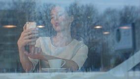 Lächelnde junge Frau, die lustige selfies an ihrem Telefon am Café nimmt Lizenzfreies Stockbild