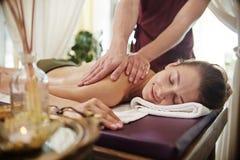 Lächelnde junge Frau, die Massage im BADEKURORT genießt stockfoto