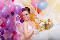 Lächelnde junge Frau, die mit Bündel Ballonen aufwirft Stockfotos