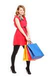 Lächelnde junge Frau, die mit Einkaufenbeuteln aufwirft Stockbild