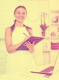 Lächelnde junge Frau, die mit Ordner mit Dokumenten steht Lizenzfreie Stockfotografie