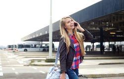 Lächelnde junge Frau, die mit Tasche und Handy reist Stockfoto