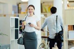 Lächelnde junge Frau, die modernes Büro verlässt lizenzfreies stockfoto