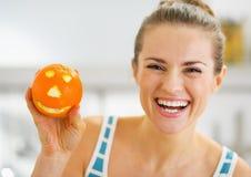 Lächelnde junge Frau, die Orange mit lustigem Gesicht zeigt Lizenzfreie Stockfotografie