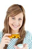 Lächelnde junge Frau, die Pillen nimmt lizenzfreie stockfotografie