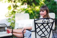 Lächelnde junge Frau, die Rest an der Gaststätte hat Stockfoto