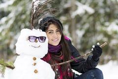 Lächelnde junge Frau, die Schneemann umarmt Stockfoto