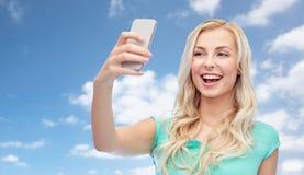 Lächelnde junge Frau, die selfie mit Smartphone nimmt Stockbilder