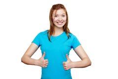 Lächelnde junge Frau, die sich Daumen zeigt stockfotografie