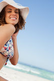 Lächelnde junge Frau, die stolz vor dem Ozean sitzt Lizenzfreie Stockfotos