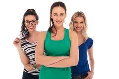 Lächelnde junge Frau, die vor ihren Freunden steht Lizenzfreies Stockbild