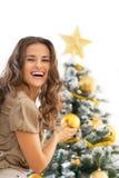 Lächelnde junge Frau, die Weihnachtsbaum verziert Stockbild