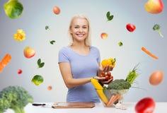 Lächelnde junge Frau, die zu Hause Gemüse kocht lizenzfreie stockfotos