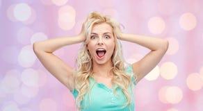 Lächelnde junge Frau, die zu ihrem Kopf oder zu Haar hält stockbild