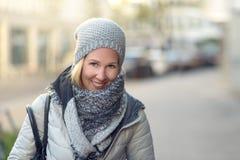 Lächelnde junge Frau in einer stilvollen Winterausstattung stockfoto
