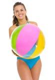 Lächelnde junge Frau im Badeanzug mit Wasserball Stockfotos