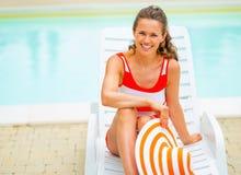 Lächelnde junge Frau im Hut, der auf sunbed sitzt Stockfoto